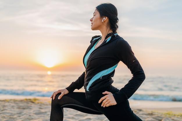 Молодая привлекательная стройная женщина делает спортивные упражнения на утреннем пляже восхода солнца в спортивной одежде, здоровом образе жизни, слушает музыку в наушниках, делает растяжку