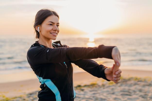 スポーツウェア、健康的なライフスタイル、イヤホンで音楽を聴き、ストレッチを作る朝日の出ビーチでスポーツエクササイズをしている若い魅力的なスリムな女性