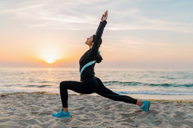 Молодая привлекательная стройная женщина делает спортивные упражнения на утреннем пляже восхода солнца в спортивной одежде, здоровом образе жизни, слушает музыку в наушниках, занимается йогой