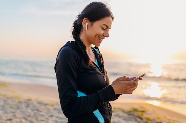Молодая привлекательная стройная женщина, делающая спортивные упражнения на утреннем пляже восхода солнца в спортивной одежде, здоровый образ жизни, слушающая музыку на беспроводных наушниках, держащая смартфон, улыбающаяся, счастливая, весело проводящая время