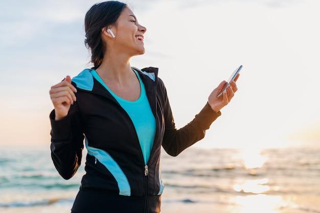 スポーツウェア、健康的なライフスタイル、スマートフォンを保持しているワイヤレスイヤホンで音楽を聴いて、楽しんで幸せに笑って朝の日の出のビーチでスポーツエクササイズをしている若い魅力的なスリムな女性