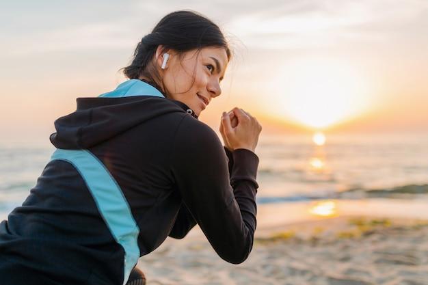 Молодая привлекательная стройная женщина делает спортивные упражнения на утреннем пляже восхода солнца в спортивной одежде, здоровом образе жизни, слушает музыку на беспроводных наушниках, делает приседания