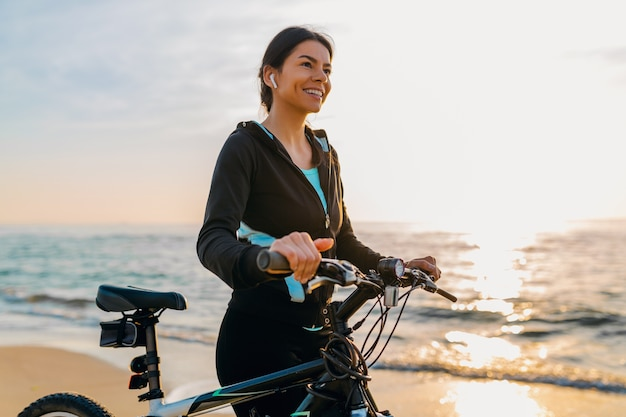 젊은 매력적인 슬림 여자 승마 자전거, 스포츠 피트니스 착용 아침 일출 여름 해변에서 스포츠, 활동적인 건강한 라이프 스타일, 행복한 재미 미소