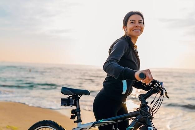 Молодая привлекательная стройная женщина, езда на велосипеде, спорт в утреннем восходе на летнем пляже в спортивной фитнес-одежде, активный здоровый образ жизни, улыбка, счастливая, весело
