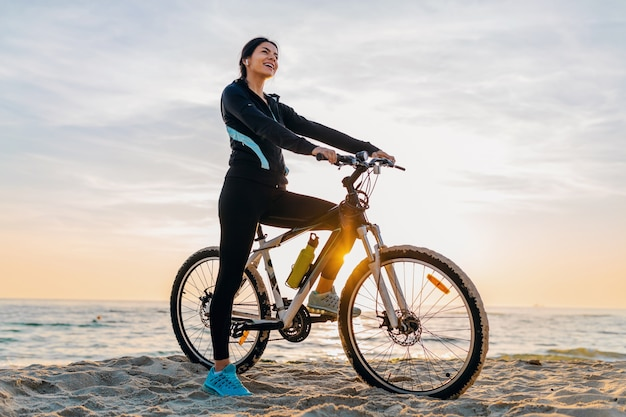 Young attractive slim woman riding bicycle, sport on morning sunrise summer beach in sports fitness wear, active healthy lifestyle, smiling happy having fun