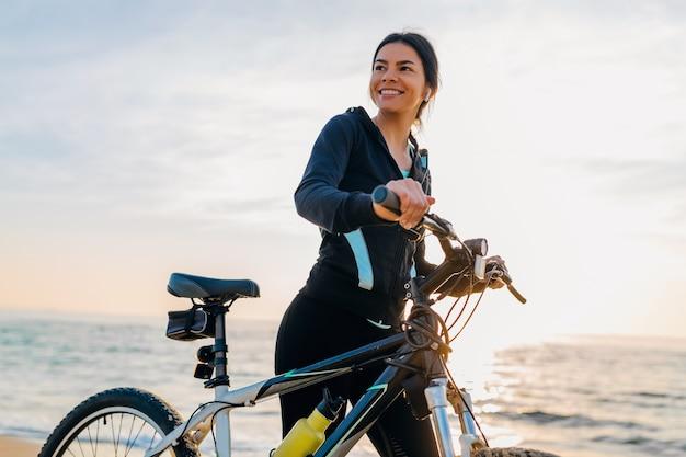 Bicicletta di guida della giovane donna sottile attraente, sport nella spiaggia di estate di alba di mattina nell'usura di idoneità di sport, stile di vita sano attivo, sorridendo felice divertendosi