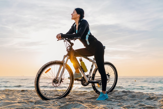 젊은 매력적인 슬림 여자 승마 자전거, 스포츠 피트니스 착용 아침 일출 여름 해변에서 스포츠, 활동적인 건강한 라이프 스타일, 행복한 재미 미소 무료 사진
