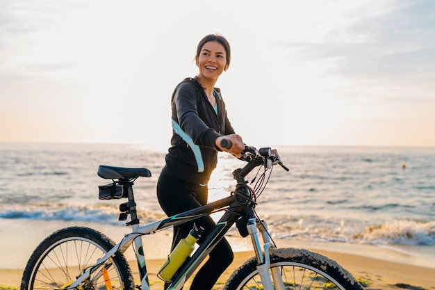 Young attractive slim woman riding bicycle, sports on morning sunrise beach in sports fitness sport clothes, active healthy lifestyle, smiling happy having fun