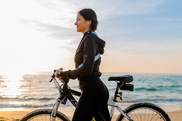 Молодая привлекательная стройная женщина, езда на велосипеде, спорт на утреннем пляже восхода солнца в спортивной фитнес-спортивной одежде, активный здоровый образ жизни, улыбка, счастливая, весело