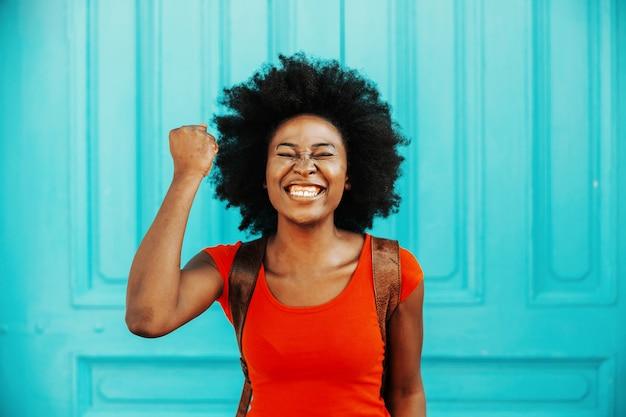 成功を祝い、拳を持っている短い巻き毛の若い魅力的な笑顔のアフリカの女性。