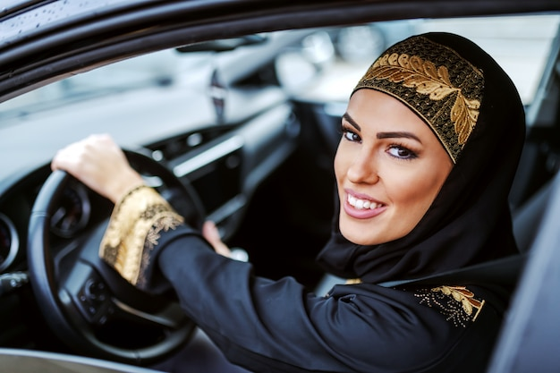 Молодая привлекательная улыбающаяся арабская женщина в традиционной одежде пробует новую машину.