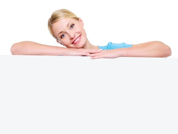 흰색 광고 판 아래 젊은 매력적인 웃는 금발 소녀