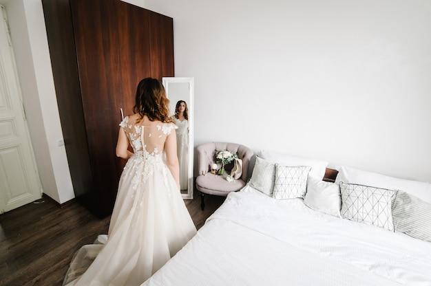 드레스에 젊은 매력적인 웃는 신부는 거울 앞에 서서 찾고 있습니다. 반사. 세로 여자. 휴일과 사랑의 개념. 결혼식 아침 준비. 배면도.