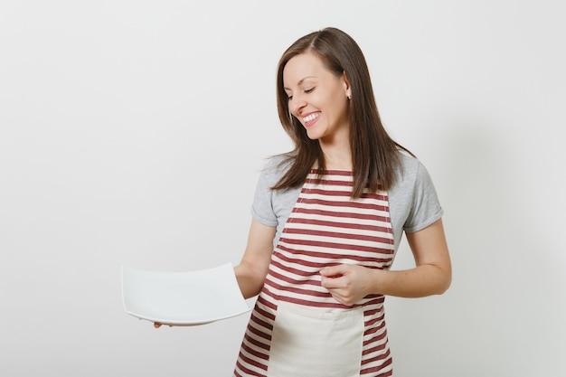 줄무늬 앞치마, 고립 된 회색 티셔츠에 젊은 매력적인 웃는 갈색 머리 백인 주부. 흰색 빈 접시를 들고 아름 다운 가정부 여자