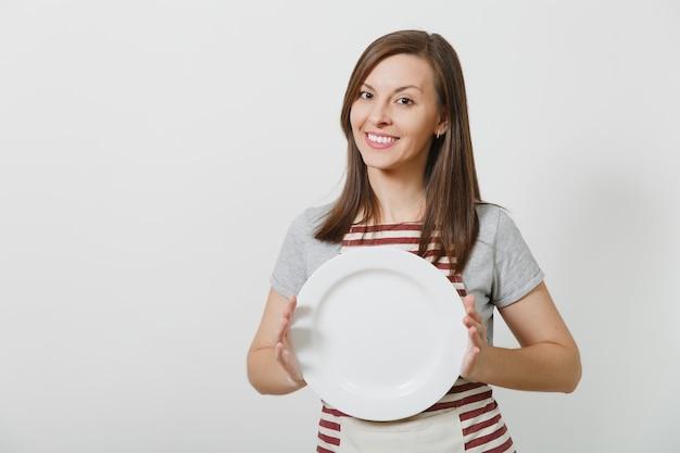 Домохозяйка молодого привлекательного усмехаясь брюнет кавказская в полосатом фартуке, серой изолированной футболке. красивая домработница женщина держит белую пустую тарелку