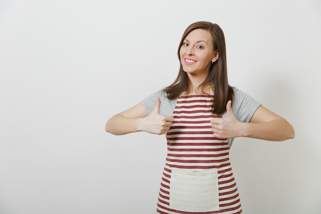 Домохозяйка молодого привлекательного усмехаясь брюнет кавказская в полосатой изолированной фартуке. красивая женщина экономки показывает палец вверх.