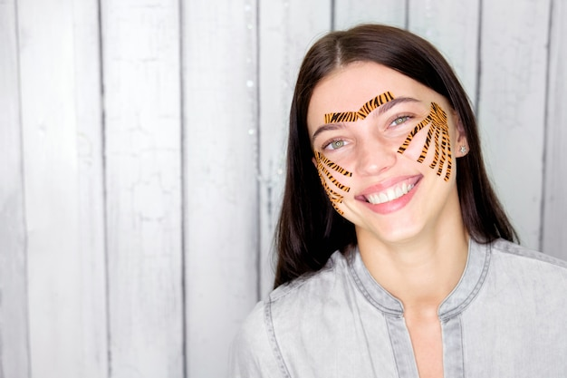 Young attractive smiling brunette woman with tiger colored tapes after taping face procedure in beauty parlor