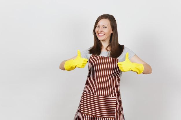 Молодая привлекательная усмехаясь кавказская домохозяйка в полосатом фартуке, желтых изолированных перчатках. женщина красивая домработница показывает палец вверх