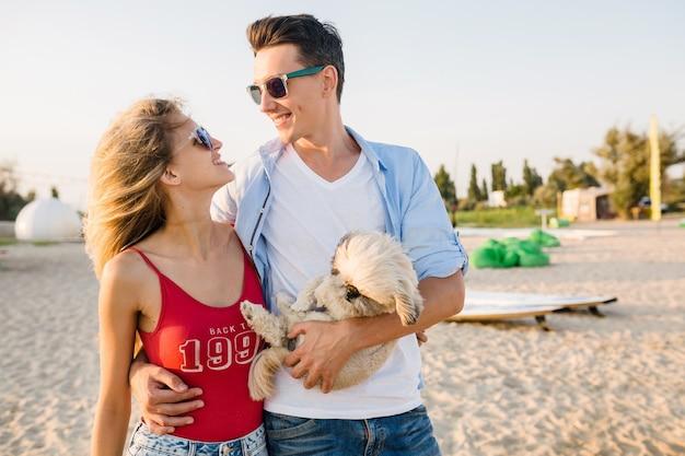 강아지와 함께 노는 해변에서 재미 젊은 매력적인 웃는 부부