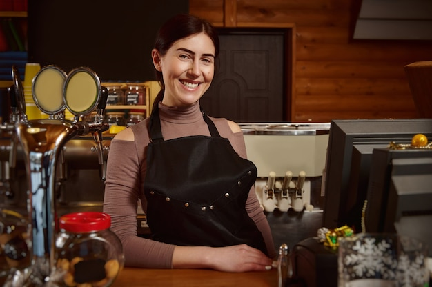 Young attractive smiling female barista in apron standing behind the bar