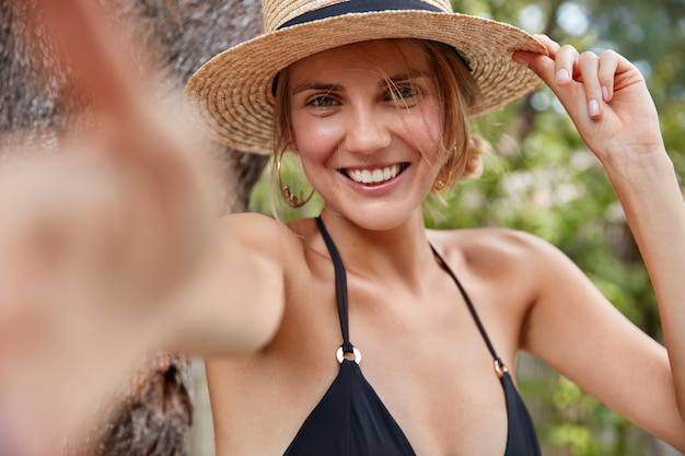 Young attractive smiling female traveler in straw hat and bikini, makes selfie against tropical background, satisfied to spend summer vacation abroad in exotic country. beauty and rest concept
