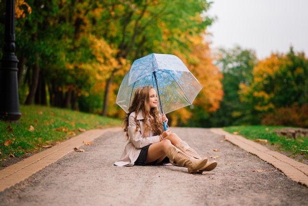 Young attractive smiling girl under umbrella in an autumn forest