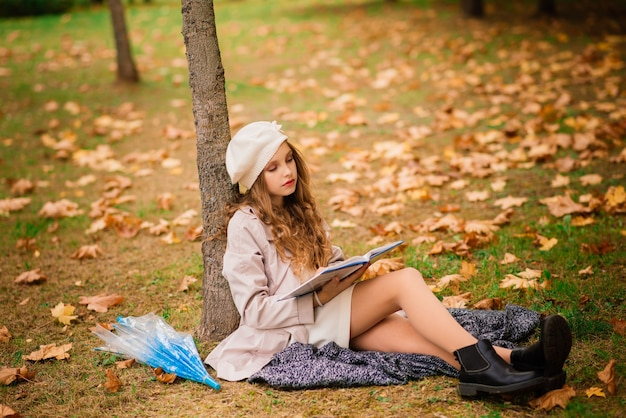 Young attractive smiling girl under umbrella in autumn forest