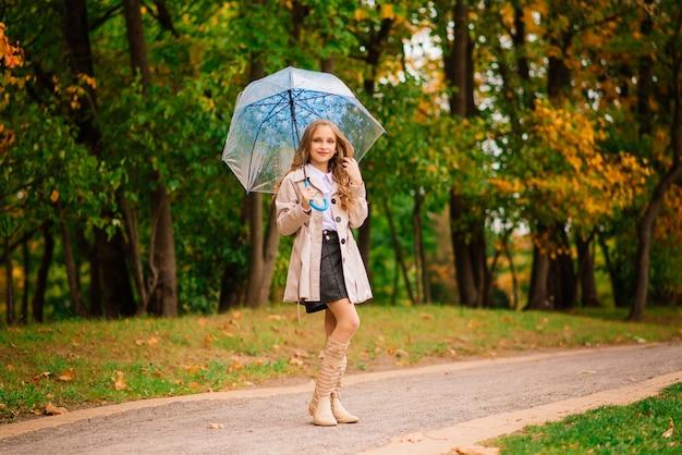 秋の森の傘の下で若い魅力的な笑顔の女の子
