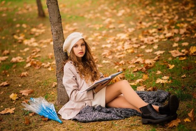 Молодая привлекательная улыбающаяся девушка под зонтиком в осеннем лесу