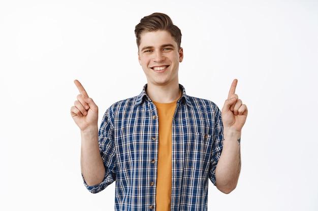 若い魅力的な笑顔の男、さまざまな割引を脇に指を指している大学生の男の子は、白の上に立って、幸せそうに見えます。