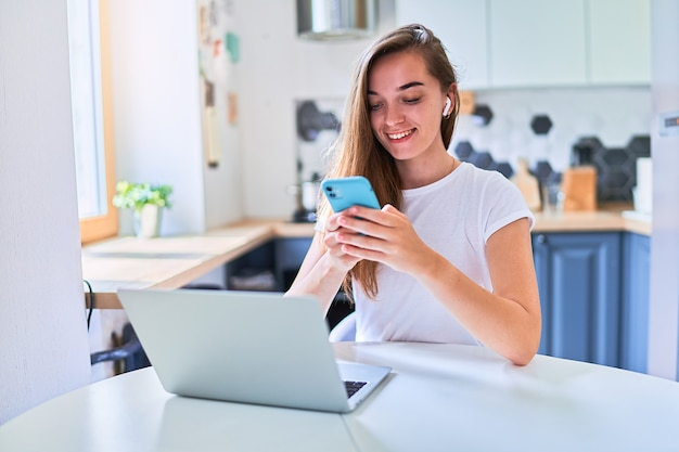 Young attractive smiling happy cute millennial girl sits by the table and using a laptop and phone for chatting online, web surfing, browsing and social networks at home