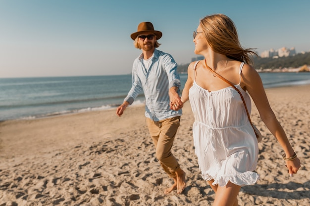 Young attractive smiling happy man in hat and blond woman in white dress running together on beach