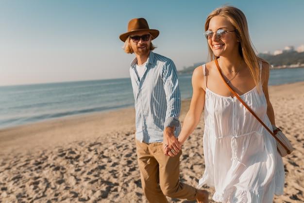 若い魅力的な笑顔幸せな男の帽子とビーチで一緒に実行されている白いドレスを着た金髪の女性
