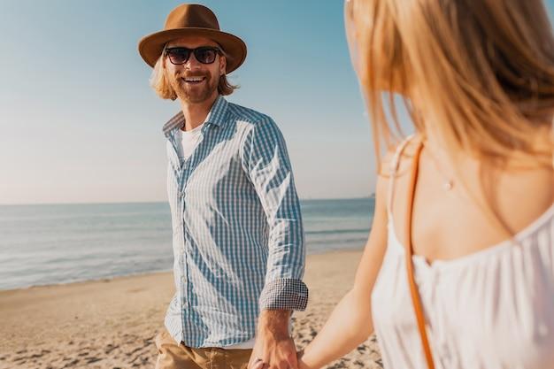 Молодой привлекательный улыбающийся счастливый мужчина в шляпе и белокурая женщина в белом платье вместе бегают на пляже
