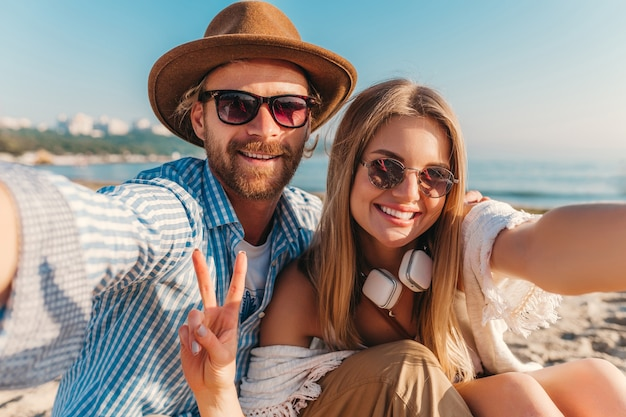 Young attractive smiling happy man and woman in sunglasses sitting on sand beach taking selfie photo