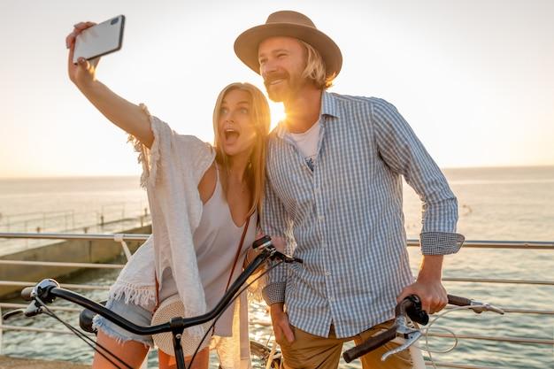 Giovane attraente sorridente felice uomo e donna che viaggiano in bicicletta prendendo selfie foto sulla fotocamera del telefono, coppia romantica in riva al mare sul tramonto, vestito stile boho hipster, amici che si divertono insieme