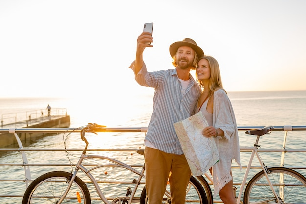 Young attractive smiling happy man and woman traveling on bicycles taking selfie photo on phone camera, romantic couple by the sea on sunset, boho hipster style outfit, friends having fun together