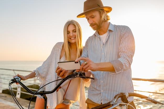Giovane attraente sorridente felice uomo e donna che viaggiano in bicicletta utilizzando smartphone, coppia romantica in riva al mare sul tramonto, vestito stile boho hipster, amici che si divertono insieme