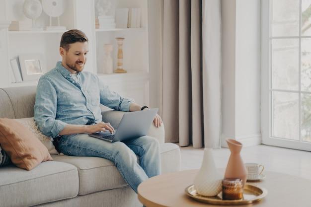 Молодой привлекательный улыбающийся мужчина-фрилансер сидит на удобном бежевом диване дома, используя ноутбук и проверяет свою электронную почту, работая удаленно в выходные дни, в повседневной одежде
