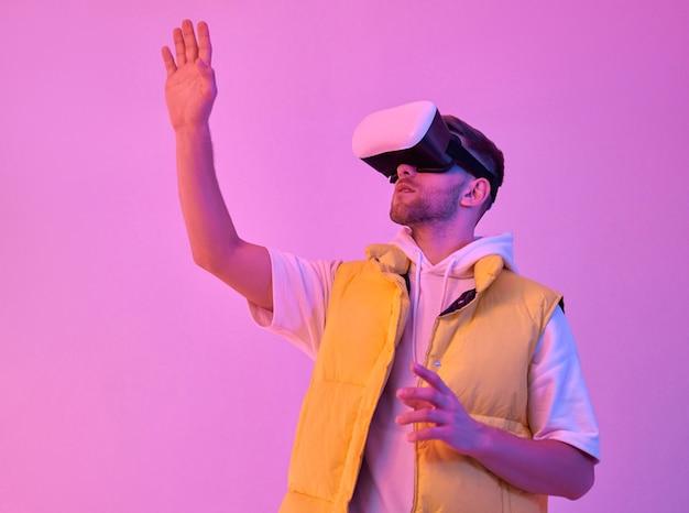 カジュアルな服を着た若い魅力的な笑顔の男は、仮想現実のメガネを使用して、ネオンピンクで隔離された彼の手で何かに触れようとしています