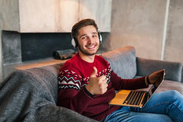Attraente giovane uomo sorridente sul divano di casa in inverno in cuffie, indossa un maglione lavorato a maglia rosso, lavorando su laptop, libero professionista, felice, positivo, mostrando il pollice in alto
