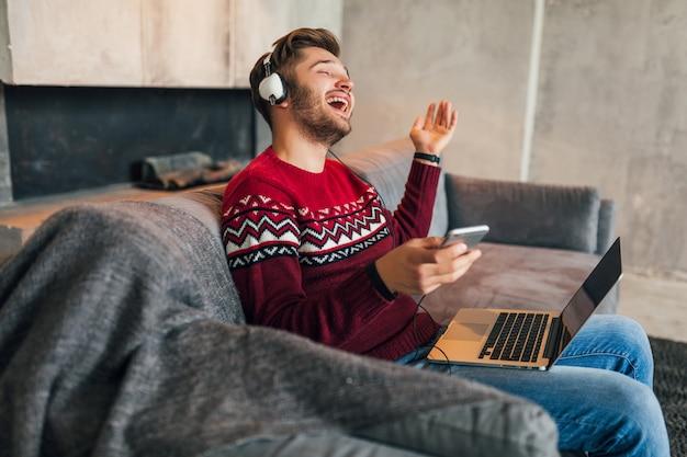 Giovane uomo sorridente attraente sul divano di casa in inverno cantando alla musica sulle cuffie, indossa un maglione lavorato a maglia rosso, lavorando sul computer portatile, libero professionista, emotivo, ridendo, felice