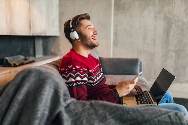 Young attractive smiling man on sofa at home in winter singing to music on headphones, wearing red knitted sweater, working on laptop, freelancer, emotional, laughing, happy