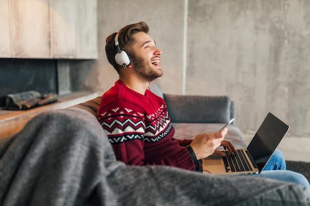 Giovane uomo sorridente attraente sul divano a casa in inverno cantando alla musica sulle cuffie, indossa un maglione lavorato a maglia rosso, lavora al computer portatile, libero professionista, emotivo, ridendo, felice