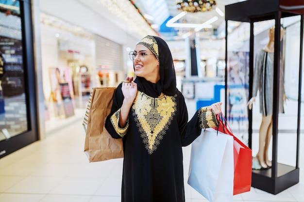伝統的な摩耗の若い魅力的な笑顔のイスラム教徒の女性が手に買い物袋を持つショッピングモールに立って、店の窓を見ています。