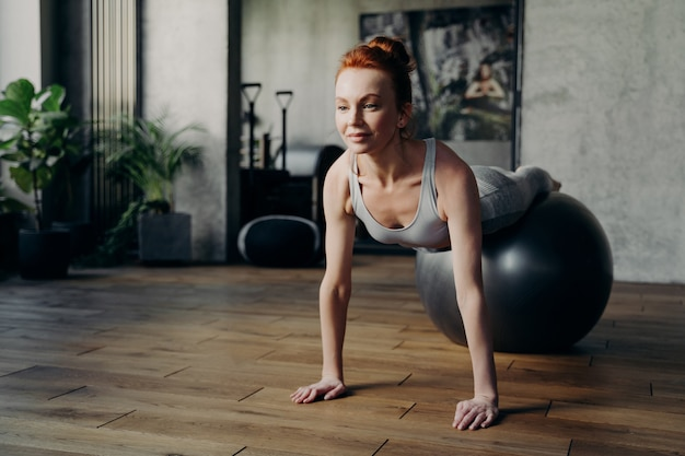 피트 니스 스튜디오에서 훈련 하는 젊고 매력적인 미소 빨간 머리 여성, 운동 공에 누워 바닥을 기반으로 똑바로 팔로 팔 굽혀 펴기를 하는 운동을 하는 동기 부여 여성 피트볼과 함께 운동