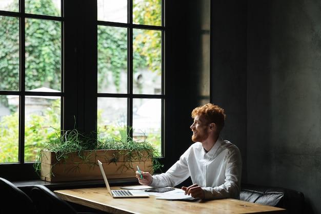 Молодой привлекательный улыбающийся рыжий бородатый деловой человек, глядя на окна, сидя на рабочем месте