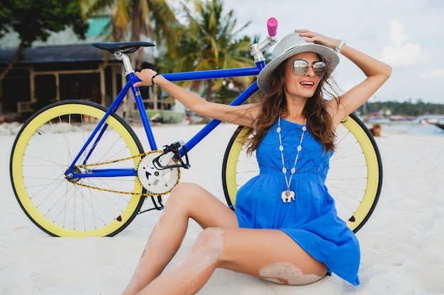 Giovane donna sorridente attraente in vestito blu che si siede sulla sabbia sulla spiaggia tropicale con la bicicletta che indossa cappello e occhiali da sole