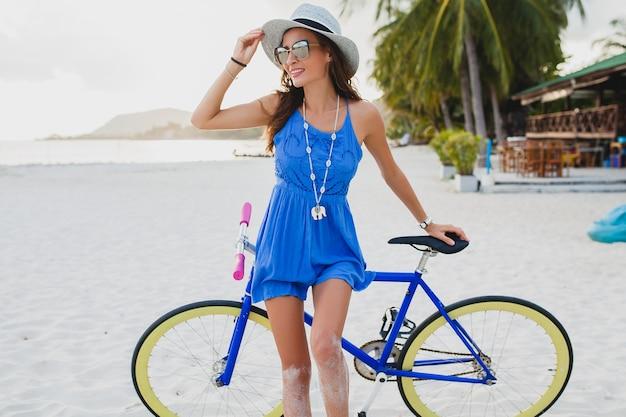 Giovane donna sorridente attraente in vestito blu che cammina sulla spiaggia tropicale con la bicicletta che indossa cappello e occhiali da sole