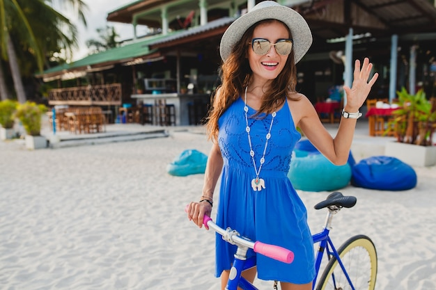 Young attractive smiling woman in blue dress walking on tropical beach with bicycle wearing hat and sunglasses